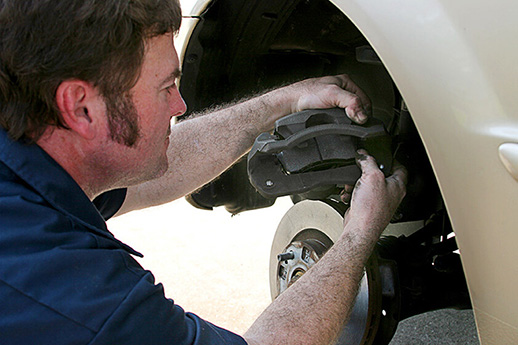 Mechanic Inserting Brake Pad